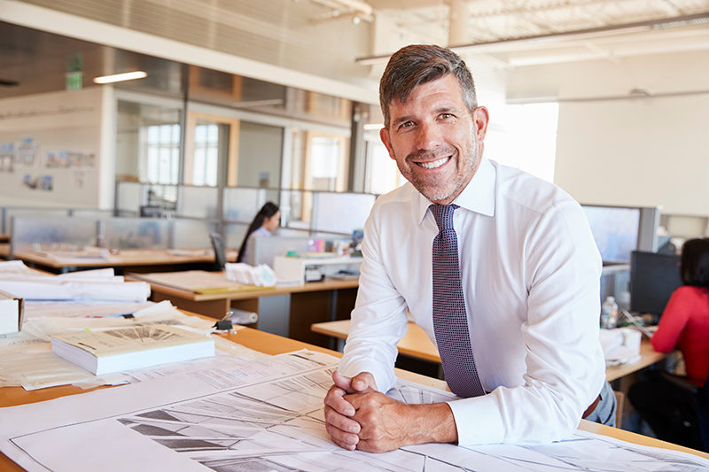 Middle aged male architect smiling to camera in his office