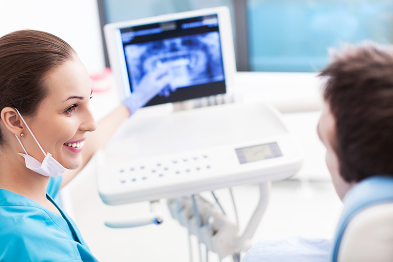 Smiling dentist explaining X-ray procedure to patient